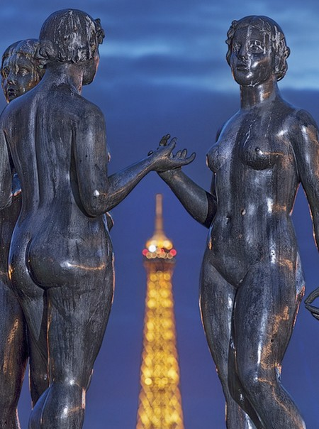 The Eiffel Tower seen behind a group of three statues entitled «Les Trois Grâces», made by Aristide Maillol in 1938. The statues were set in the Jardin des Tuileries in 1964, then moved to the Jardin du Carrousel in 1995.
